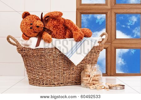 Laundry basket with freshly laundered white towels and teddy bear