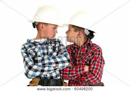 Two Young  Brothers Sneering At Each Other Wearing Construction Hardhats