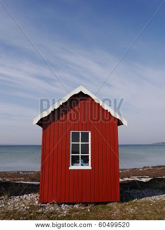 Cute red beach hut on Danish island of Aero against background of sea and windswept blue sky