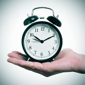 someone holding an alarm clock adjusting forward one hour for the summer time poster