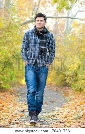Young smiling man walking in autumn park.