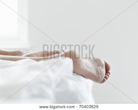 Young woman lying in bed with closeup of barefeet