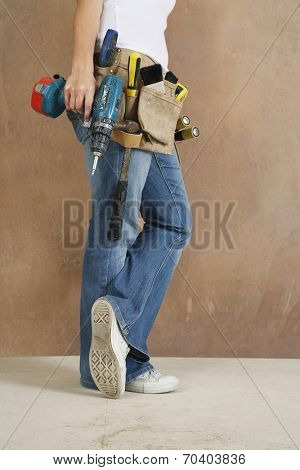 Lowsection side view of a woman with toolbelt and drill leaning against wall