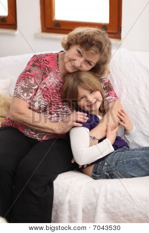 Little Girl With Grandmother On Sofa