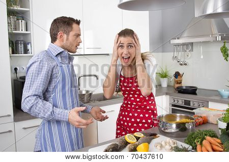 Young Couple Screaming At Home In The Kitchen.