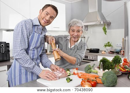 Young Man And Older Woman Cooking Together In The Kitchen.