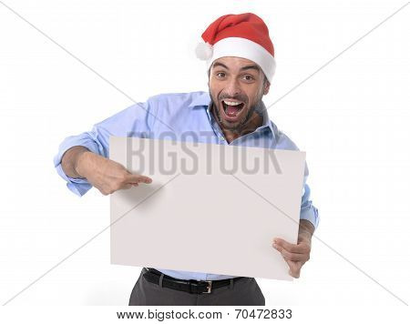Handsome Business Man In Santa Christmas Hat Pointing Blank Billboard