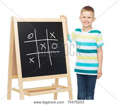 people, childhood and education concept - smiling little boy with blank blackboard over white background