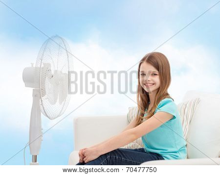 summer, weather and equipment concept - smiling little girl sitting on sofa with big fan at home