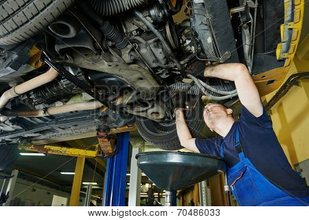 car garage auto mechanic repairman tighten screw with spanner during automobile maintenance at repair service station