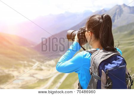 woman photographer taking photo at plateau mountain peak in tibet,china