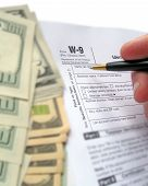 fill out the revenue W-9 Tax form for 2010 year by black pen. tax deduction concept poster