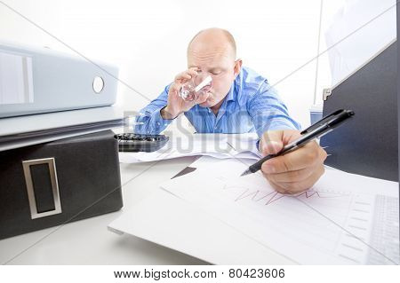 Tired and exhausted businessman drinks water