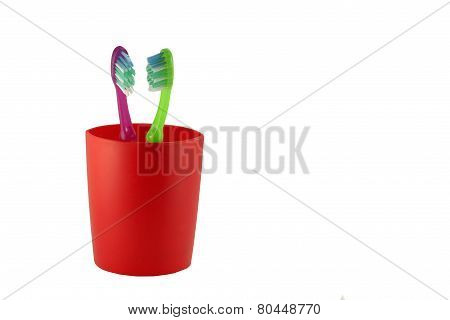 two tooth brushes in red glass