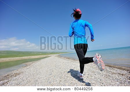 Runner athlete running on stone beach of qinghai lake. woman fitness jogging workout wellness concept. poster