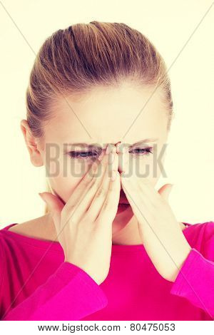 Young caucassian woman is having sinus pressure, touching her nose.