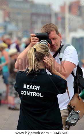 Male Photographer Taking Photo Of Female Beach Attendant