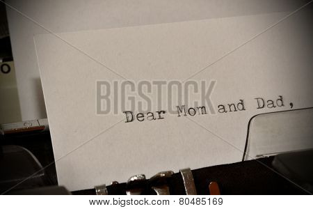 Letter with a title Dear Mom and Dad typed on old typewriter poster