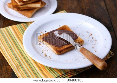Toast bread spread with chocolate on plate with knife and napkin on wooden table background