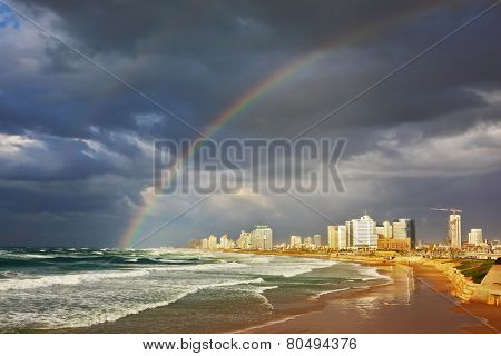 Storm cloud hanging over the sea, gorgeous huge rainbow crossed the sky. Promenade and beach in Tel Aviv