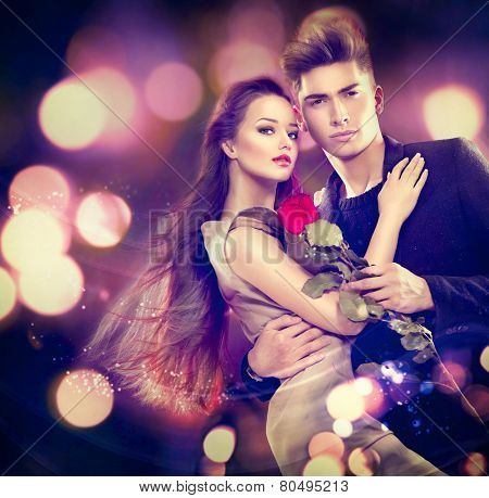 Valentine couple in love. Beauty fashion model girl with handsome model guy dancing together. Glamour couple, romantic date. Saint Valentine's day concept
