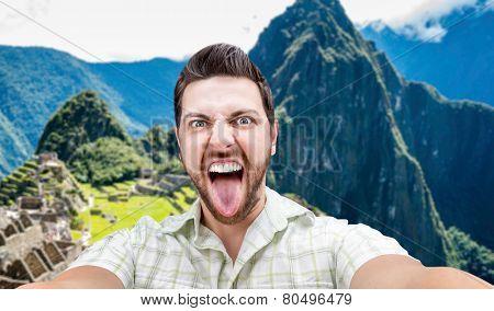Happy young man taking a selfie photo in Macchu Picchu, Peru