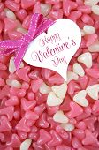Valentines Day pink and white heart shape jelly candy confectionary on pink wood background with heart greeting card and sample text - vertical. poster