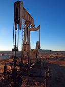 Pumping hydrocarbons at a desert well on a winter afternoon. poster