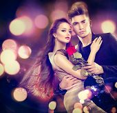 Valentine couple in love. Beauty fashion model girl with handsome model guy dancing together. Glamour couple, romantic date. Saint Valentine's day concept poster
