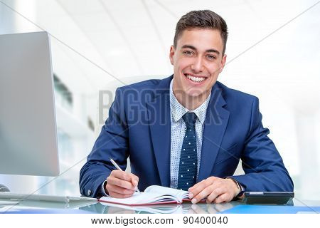 Handsome Businessman At Desk In Office.