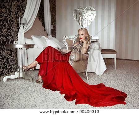 Beautiful Adult Woman In Fashion Red Dress Sitting On Modern Armchair At Luxurious Interior Apartmen