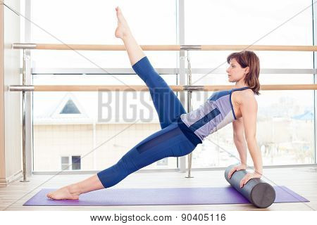 fitness, sport, training and lifestyle concept -  woman doing pilates on the floor with foam roller poster
