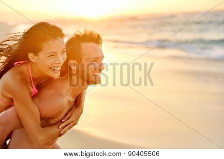 Lovers couple in love having fun piggybacking on date on beach. Portrait beautiful healthy young adults girlfriend and boyfriend hugging happy. Multiracial dating or healthy relationship. From Hawaii.