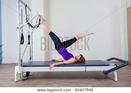 gym woman pilate instructor stretching in reformer bed poster