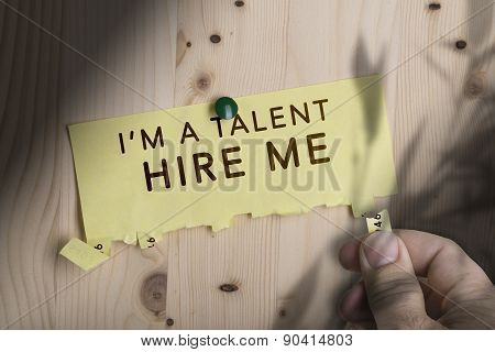 The text hire me pinned to wooden notice board. Concept for summer job and talent hiring poster