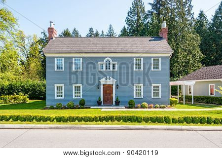 Luxury blue house with beautiful landscaping on a sunny day. Home exterior.