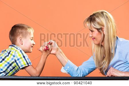 Family children and motherhood concept. Son confronts his middle aged mother. Woman and little boy arm wrestling having fun. poster