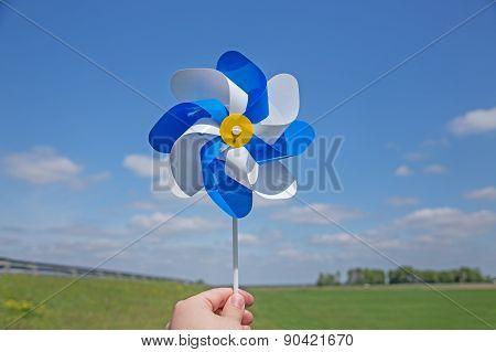 Hand holding pinwheel over horizon
