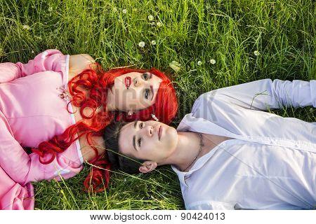 Romantic Fairy Tale Couple Sitting in Garden among Flowers