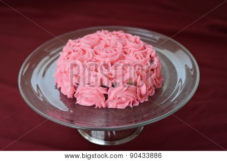 Deliciously Decorated Pink Rose Frosting Cake On A Glass Plate