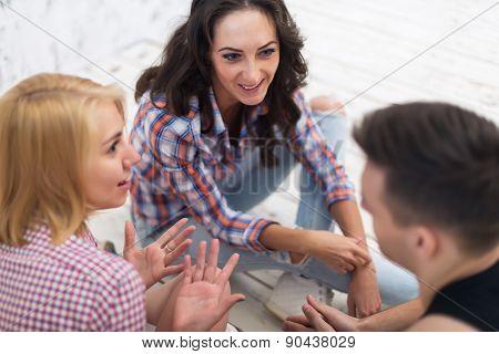 Friends two girls and guy sitting on floor in summer jeanswear street urban casual style talking, ha