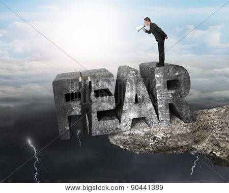 Boss using megaphone commanding employee hanging on big 3D fear mottled concrete word at the edge of cliff with opposite weather conditions background sunny sky cloudscape dark overcast lightning. poster