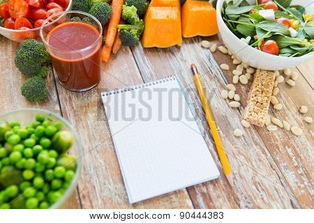 healthy eating, vegetarian food, advertisement and culinary concept - close up of ripe vegetables and notebook with pencil on wooden table