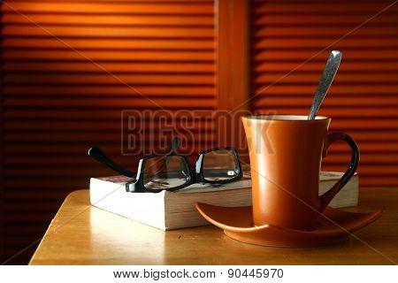 Coffee mug, eyeglasses and a book on a table