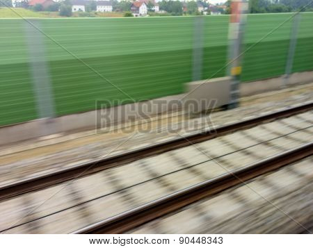 tracks and rails out in movement from a moving train. symbolic photo for train, tempo and dynamics. poster