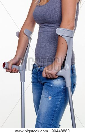 a young woman with crutches. symbolic photo for accidents, domestic accidents and insurance.