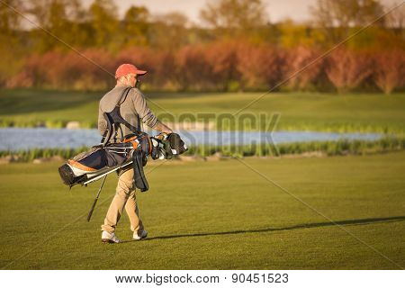 Male golf player carrying bag on fairway during sunset.
