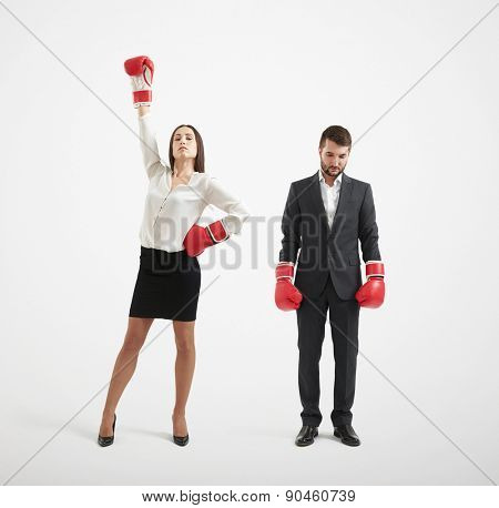 businessman loser and winner businesswoman in red boxing gloves over light grey background