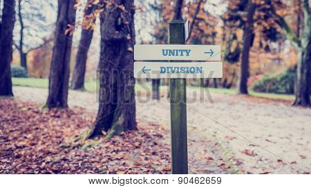 Signpost With Arrows Pointing Two Opposite Directions Towards Unity And Division