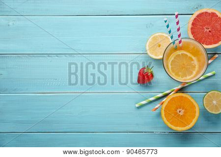 Healthy juice and fresh fruits on wood background